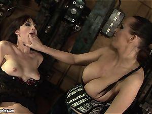 Mandy Bright finger-tickling a super hot nymph in a machine shop